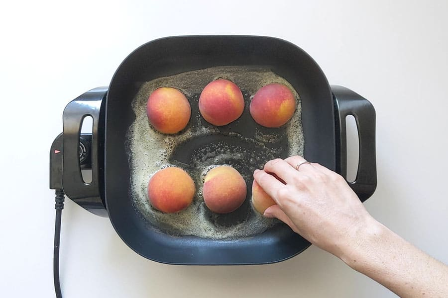 Peach halves cooking on an electric frypan.