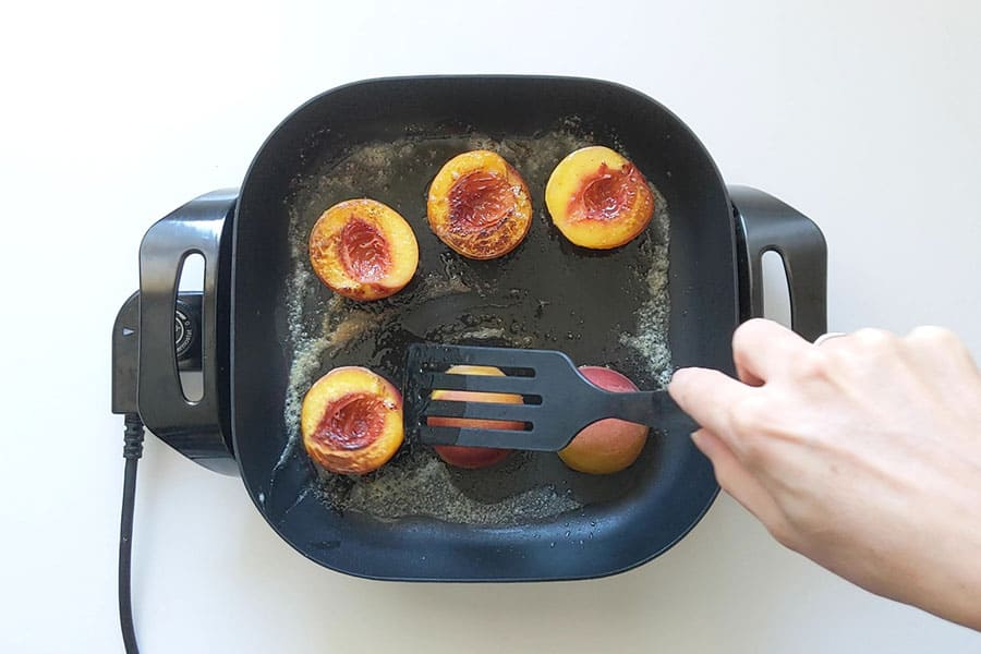 Caramelizing peach halves on an electric frypan.