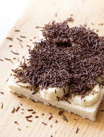 A slice of white bread on a chopping board, topped with banana and chocolate sprinkles.