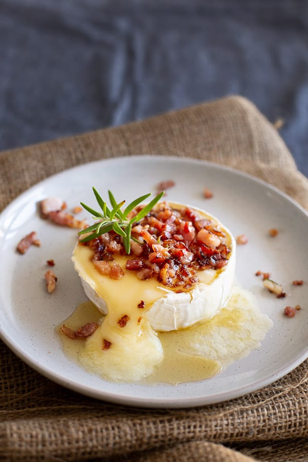 Melted and baked camembert with honey and bacon on white plate.