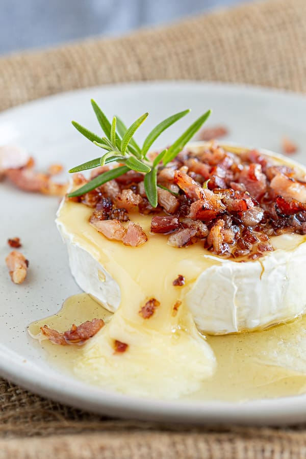 Baked camembert on a white plate with bacon and rosemary.