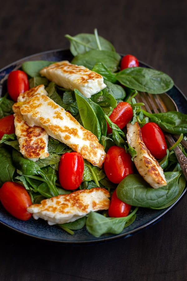 Plate of salad filled with haloumi, mint, tomatoes and mint.