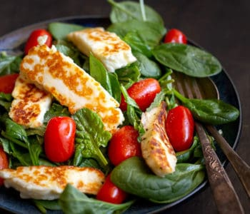 Haloumi salad in a bowl with serving fork and spoon.