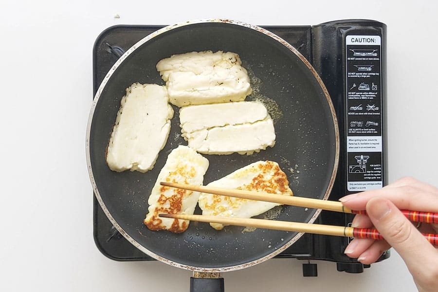Frying haloumi in a pan.