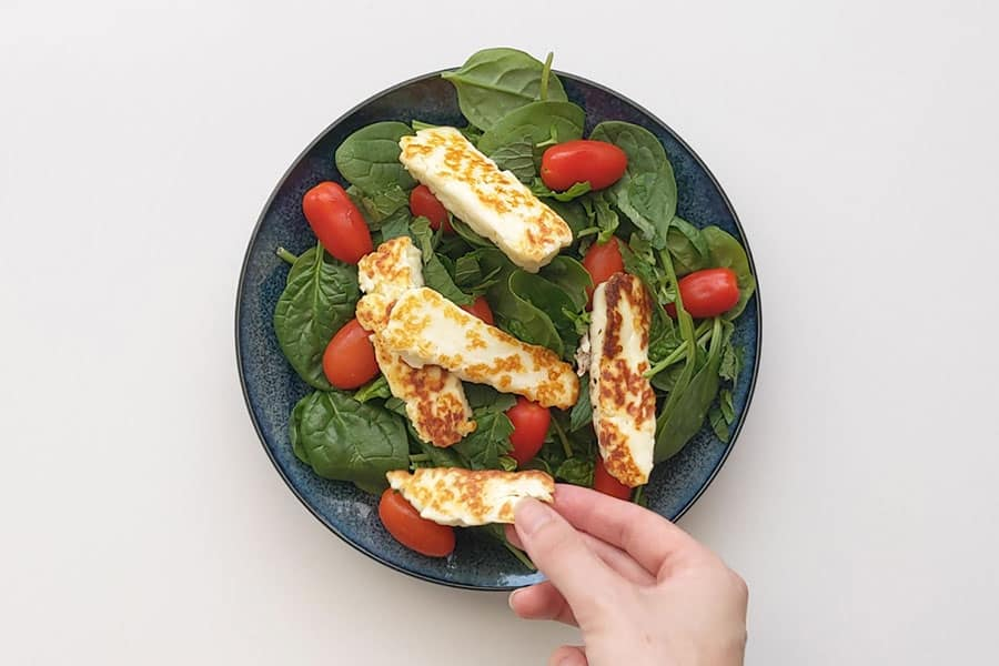 Laying fried haloumi on a bed of salad.