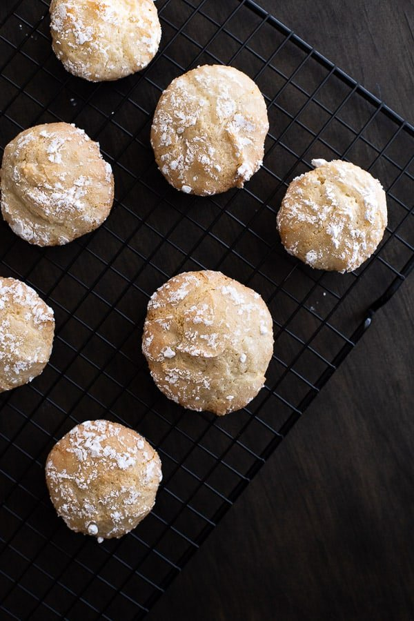 Italian almond biscuits cooling on a black rack.