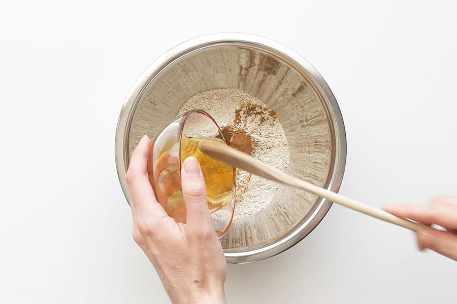 Pouring honey into dry ingredients.