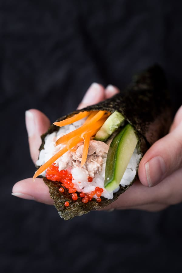 Temaki sushi held in a hand.