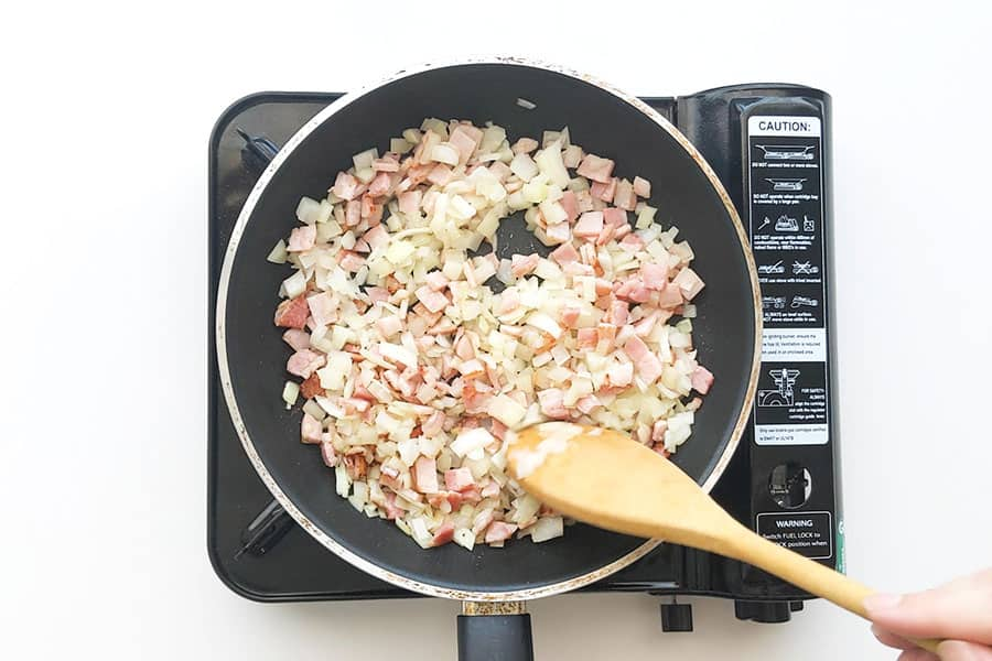Frying bacon and onion in a pan.
