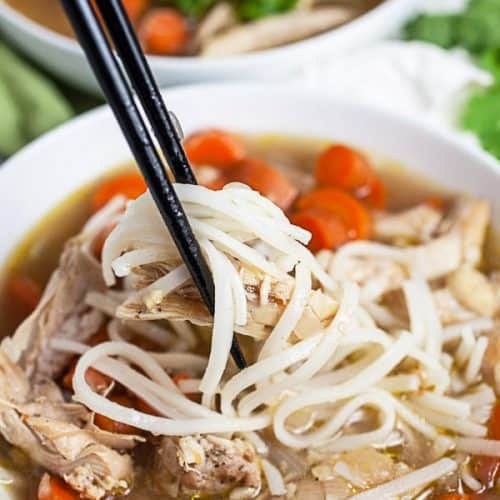Picking up noodles and chicken with chopsticks, from a bowl of Vietnamese chicken noodle soup.