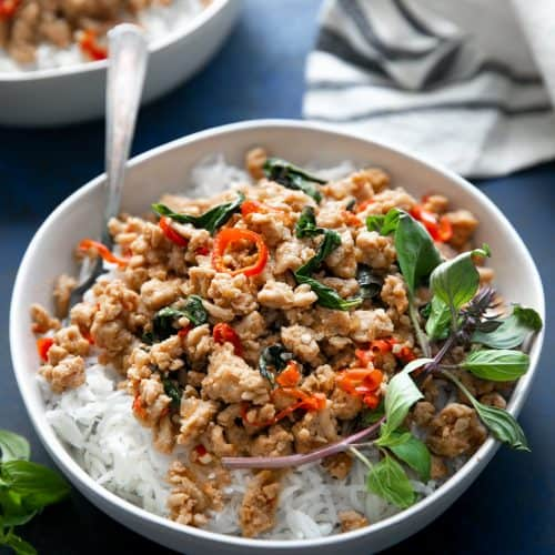A bowl of thai basil chicken served on rice, garnished with fresh thai basil.