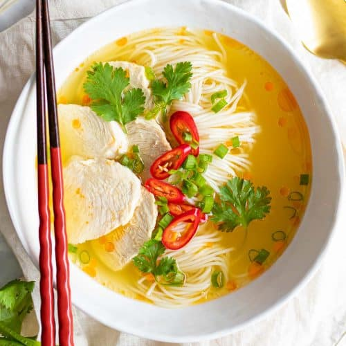 A bowl of Asian chicken noodle soup garnished with coriander and chilli