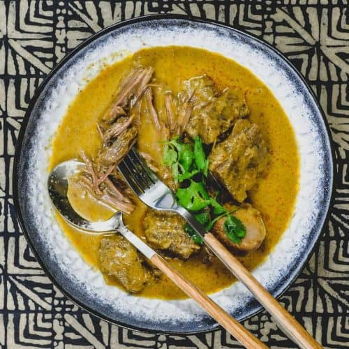 Tender beef pieces cooked in massaman curry sauce, in a bowl with a fork and spoon.