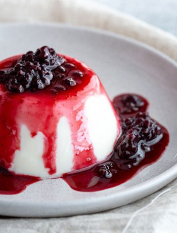 Blancmange set on a plate with blackberry coulis.