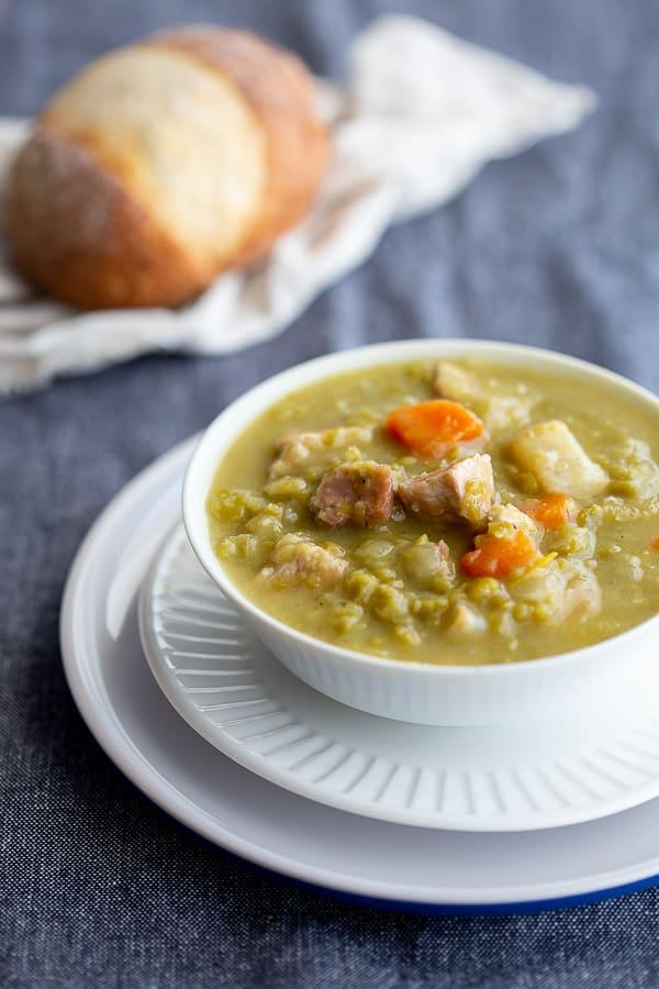 Bowl of chunky Dutch split pea soup with bread roll in background.