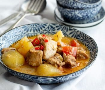 Chunky Nyonya chicken curry in a blue bowl.