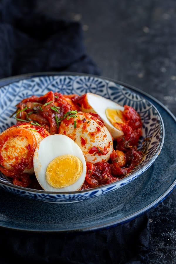 Blue bowl with eggs coated in sambal oelek sauce.