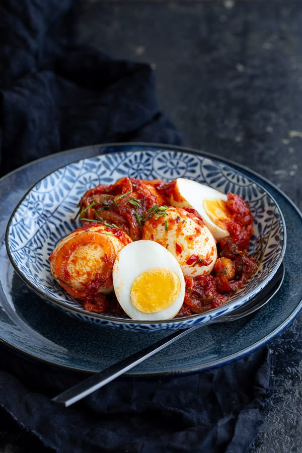 Bowl of sambal telur with plate and spoon.