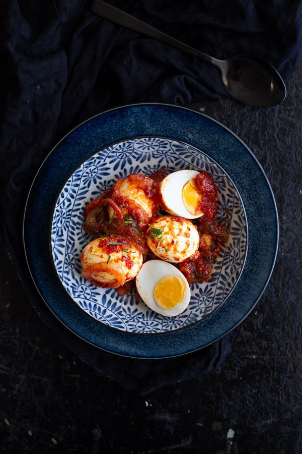 Top view of eggs coated with sambal in a bowl. One egg is cut in half.