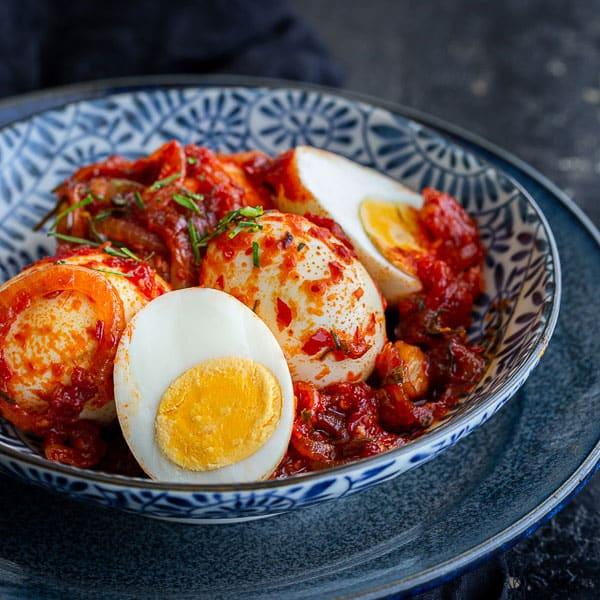 Eggs coated in Indonesian sambal oelek sauce in large blue bowl.