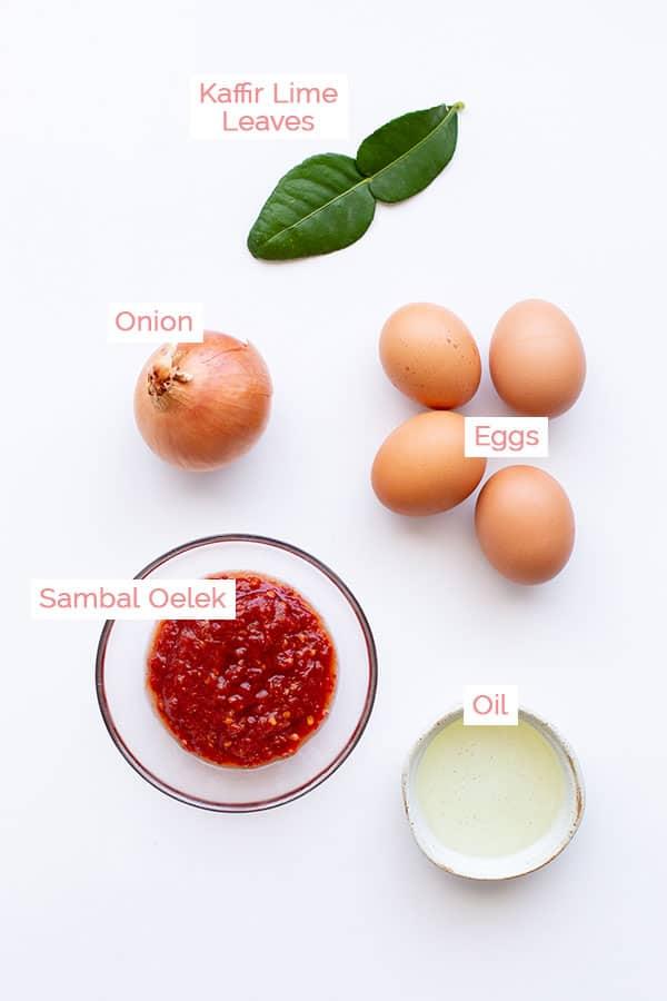 Ingredients for making sambal telur, including eggs, sambal, kaffir lime leaves and onion.