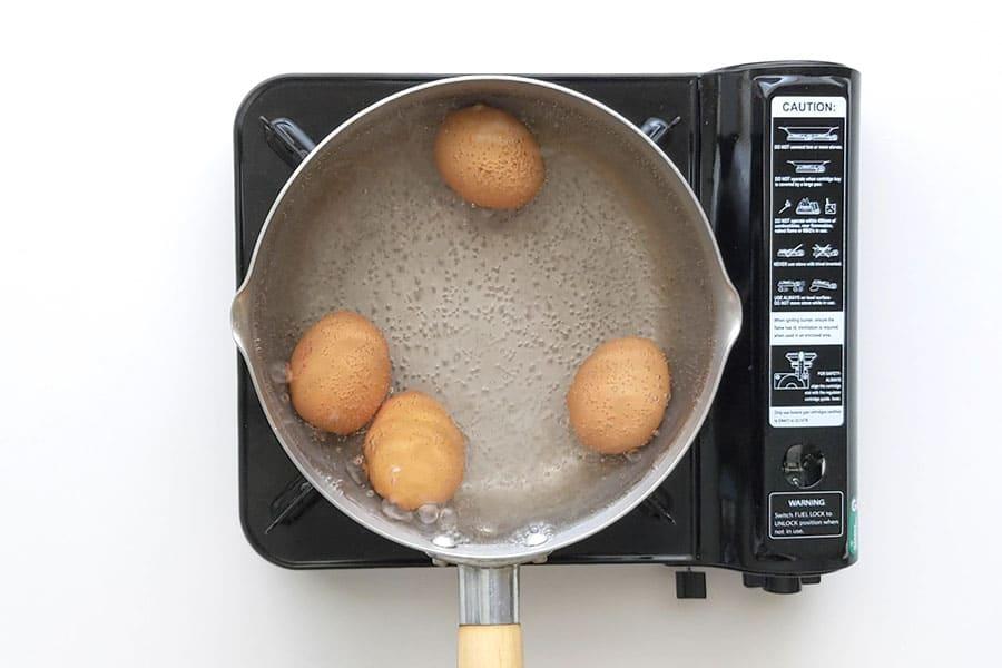 Boiling eggs in a medium saucepan.