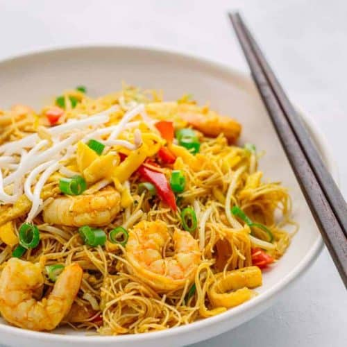 Singapore noodles with shrimp and bean shoots in a bowl, with chopsticks.