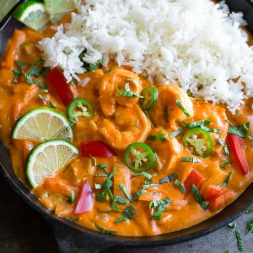 Thai shrimp curry with rice in a large dish, garnished with herbs and lime slices.