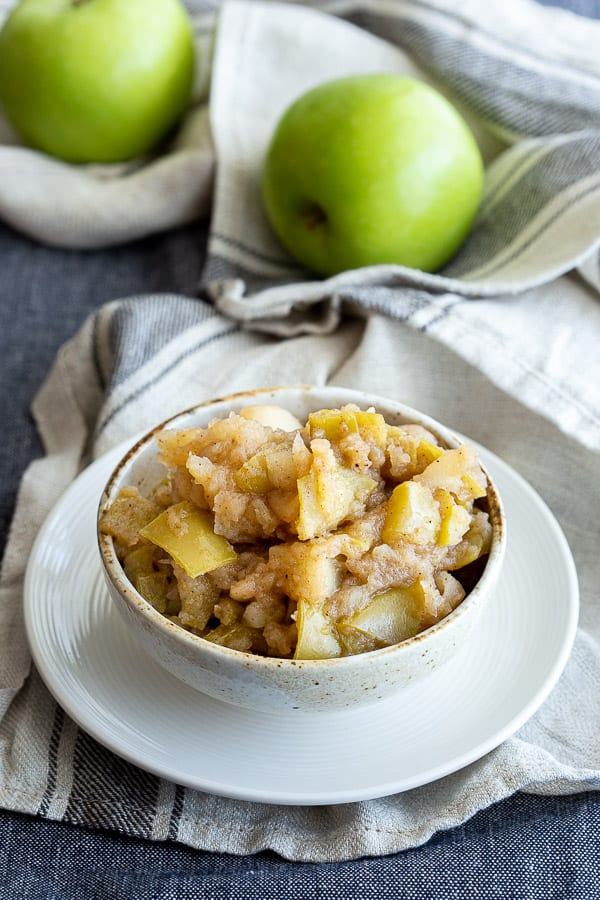 Chunky applesauce with skin on in a white bowl.