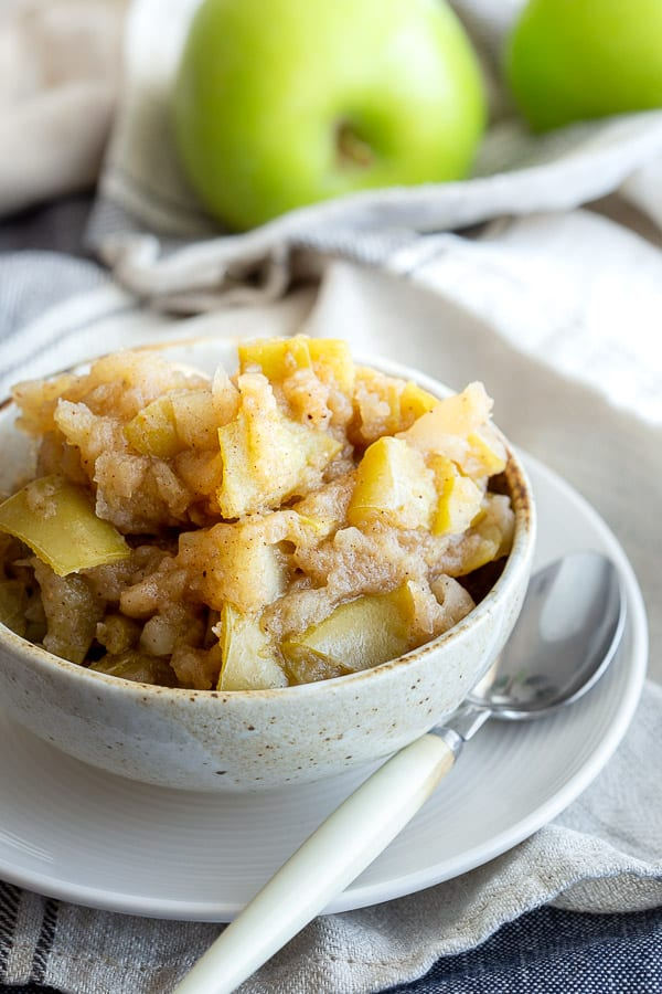 Bowl with applesauce and spoon, with fresh apples in the background.