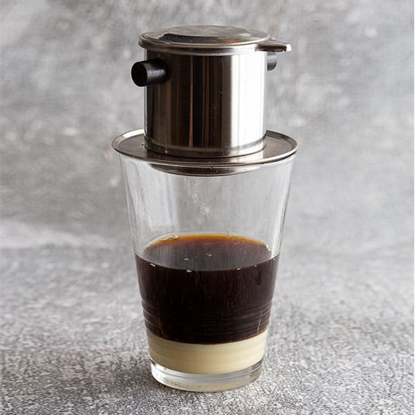 Glass filled with condensed milk and coffee, topped with Vietnamese phin filter.