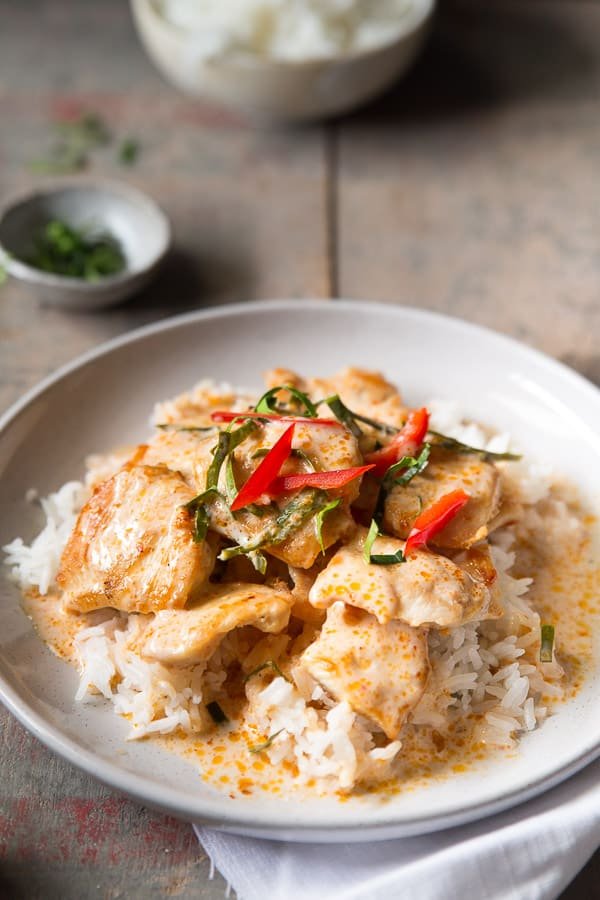 A plate of chicken curry served on rice and garnished with fresh kaffir lime leaves.