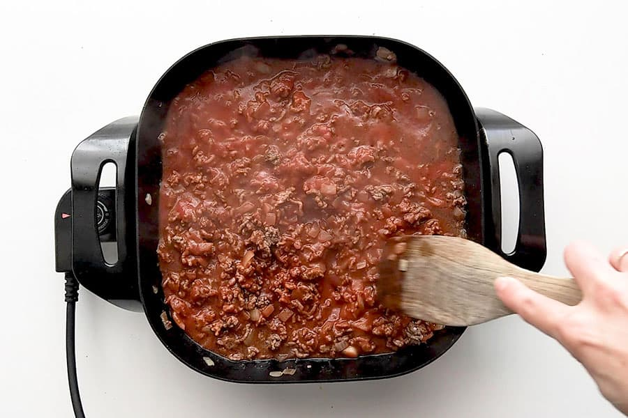 Stirring passata into beef mince.