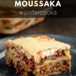 Cheesy layers of moussaka on a plate.