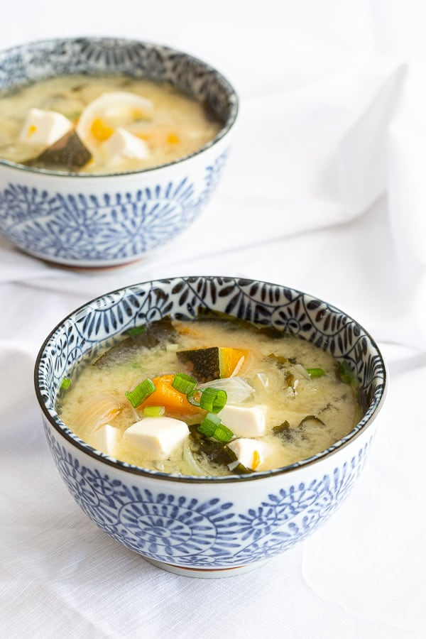 Two bowls of Japanese miso soup with chunky pumpkin and tofu.