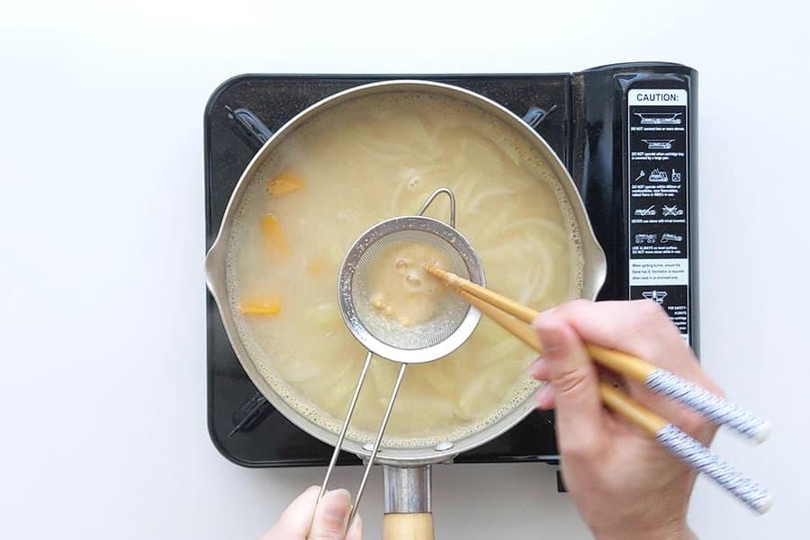 Dissolving miso paste into soup stock.
