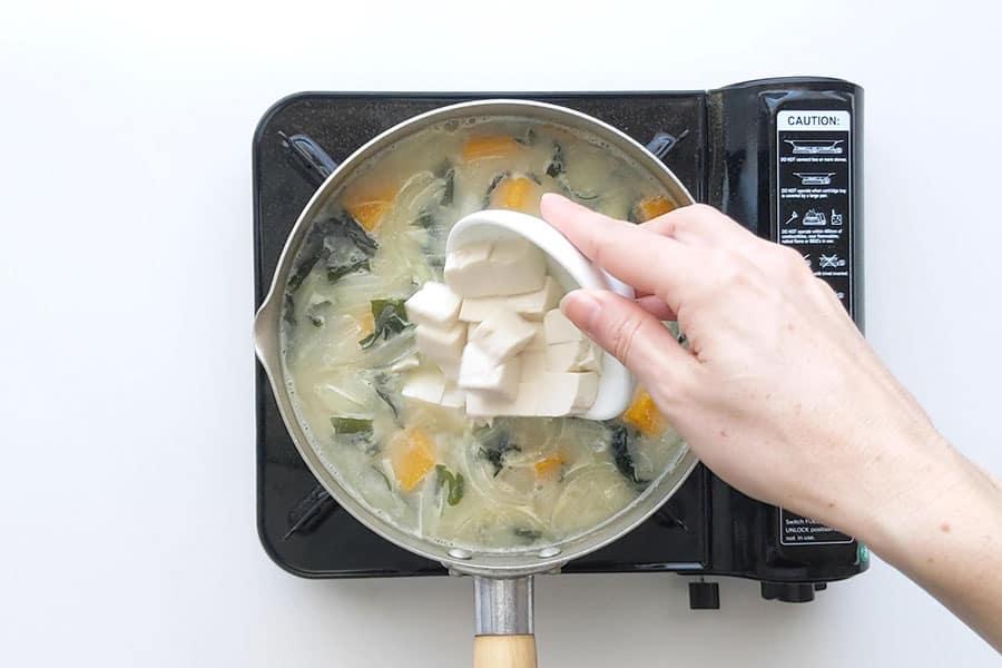 Pouring tofu into miso soup.