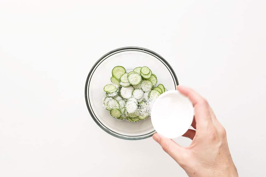 Salting the cucumber in a bowl.