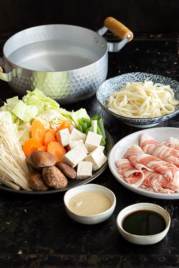 Plates of shabu shabu ingredients with dipping sauces of ponzu and sesame.