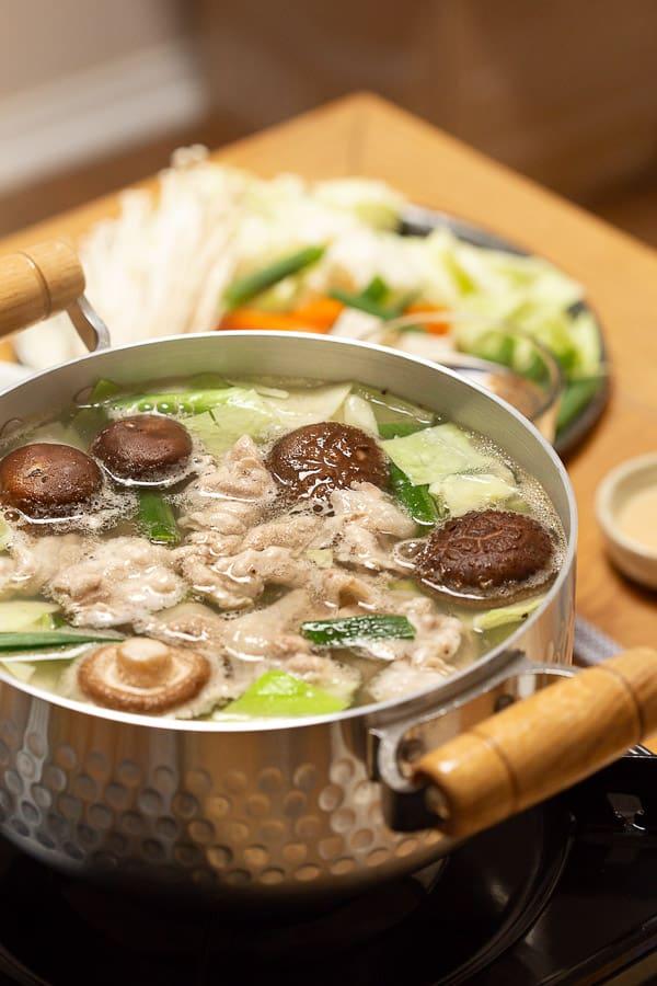 Vegetables and pork boiling in shabu shabu broth, ready to eat.
