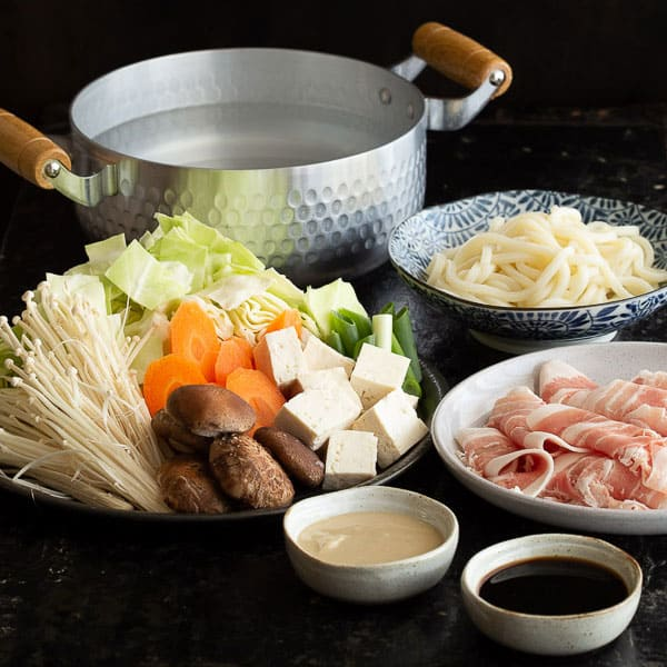 Pork, udon and vegetables all cut up and ready to eat in a shabu shabu hot pot.