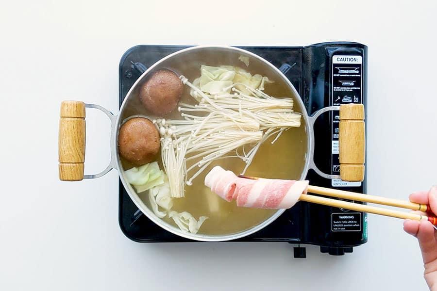 Placing a frozen slice of pork into the shabu shabu hot pot broth.
