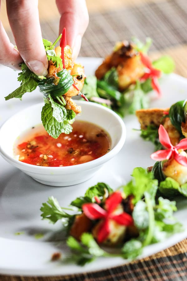 Dipping a tam huu spring onion roll into the sweet and sour dipping sauce.