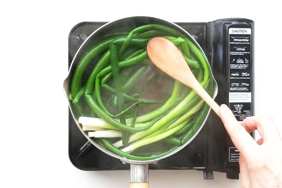 Blanching spring onions in boiling water.