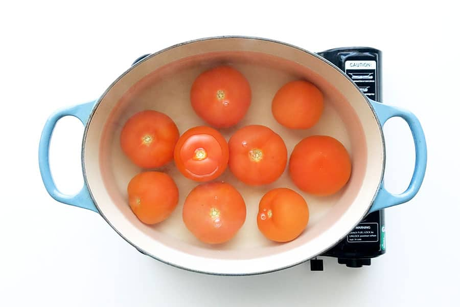 Boiling the tomatoes in water.