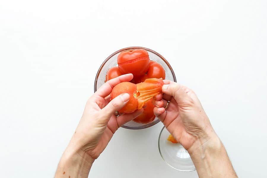 Peeling off the tomato skins ready for the pasta sauce.