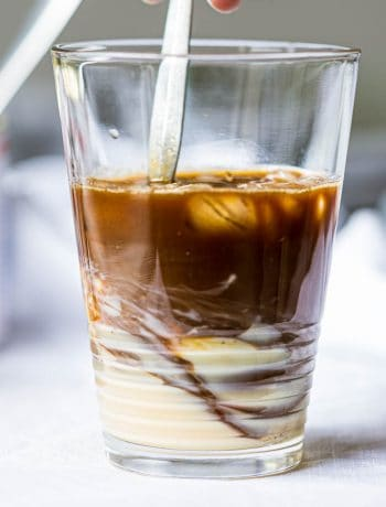 Swirling Vietnamese coffee with condensed milk in a glass.