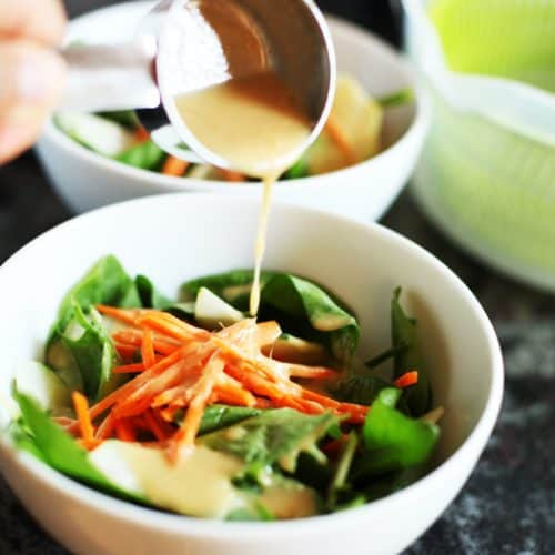 Pouring sesame ginger miso dressing over a crisp carrot and greens salad.