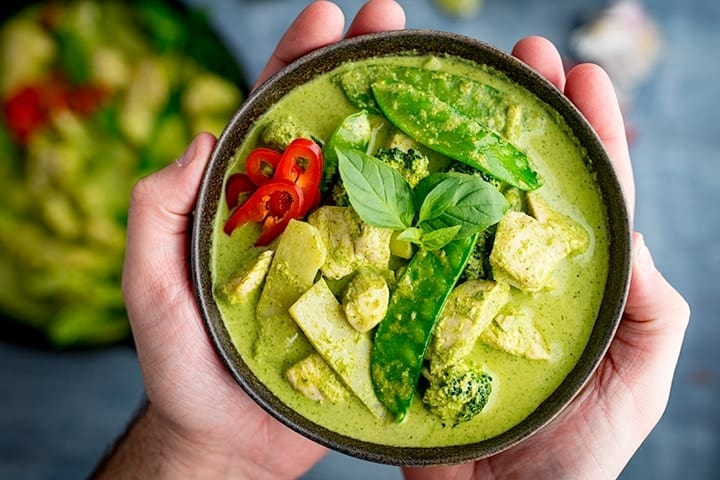 A bowl of Thai green chicken curry with fresh chilli and basil.