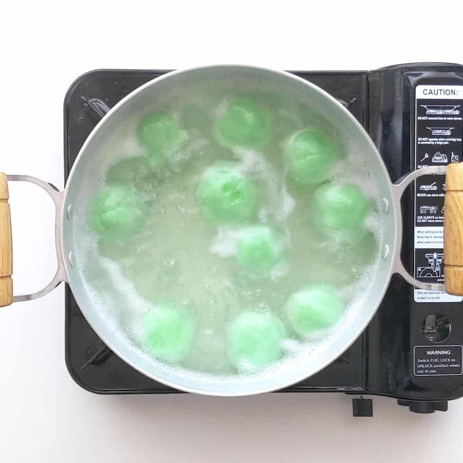 Klepon floating in boiling water, ready to remove.
